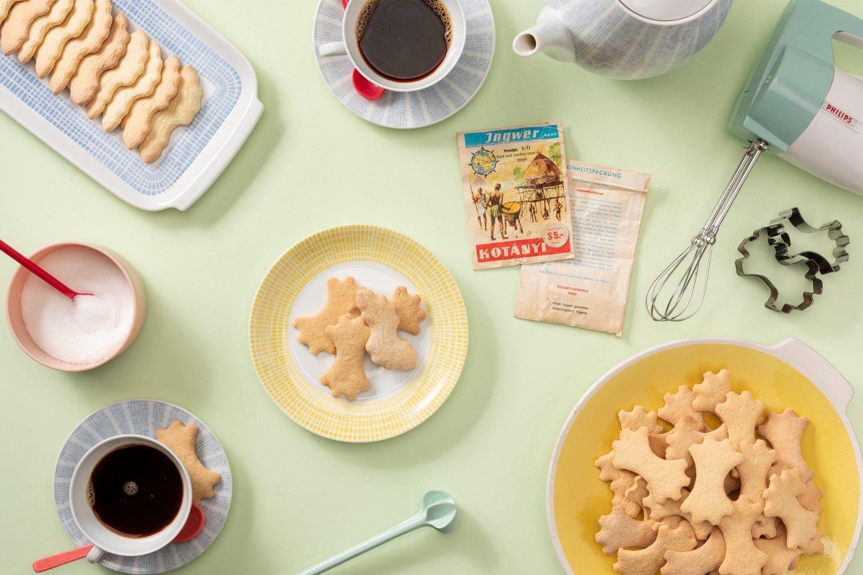 Gyömbéres kekszek desszertes tányéron és egy pasztellszínű kávéskészlet.