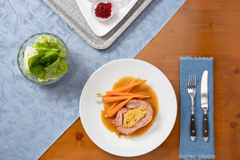 Két darab töltött borjúszegy glasszírozott sárgarépával, fehér tányéron.